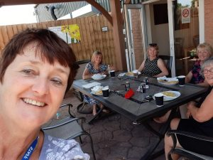 Sheila having lunch on a sunny day with 4 carers