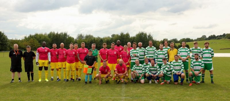 both teams positioned for the group photo. one kit is green and white striped. The other is pink shirts with yellow shorts and socks.