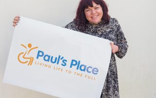 Briony May smiling holding up Paul's Place New Logo on a poster