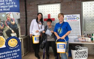 Staff and members fundraising with buckets and banners