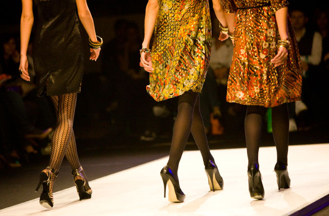 legs of 3 models walking down the catwalk
